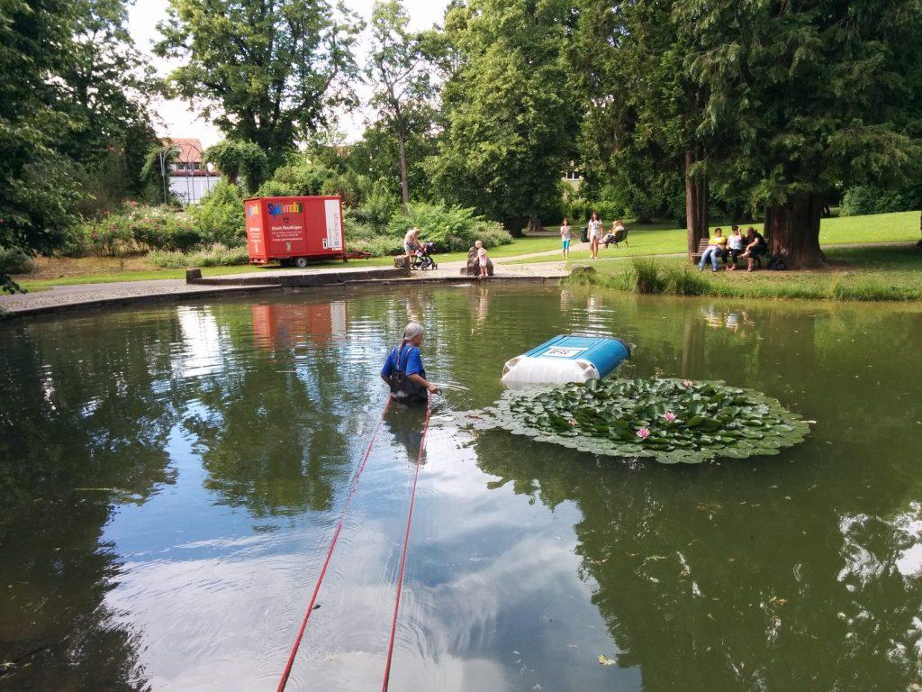 eine Person in Kanalarbeiterhosen birgt ein Dixiclo aus dem Stadtgarteteich
